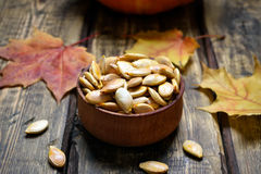 Pumpkin seeds and autumn maple leaves Stock Images