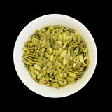 Pumpkin seeds in a bowl isolated on black Stock Image