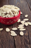 Pumpkin seeds in bowl and table Royalty Free Stock Images