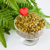 Pumpkin seeds. In a glass bowl, green leaves and a heart on white background Stock Photos