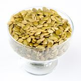 Pumpkin seeds. In a glass bowl on white background Stock Photos