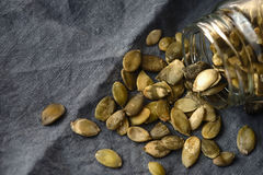 Pumpkin seeds in the glass jar  on the grey napkin Royalty Free Stock Photography