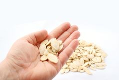 Pumpkin seeds in hand on white background Royalty Free Stock Photography