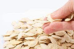 Pumpkin seeds in hand on white background Royalty Free Stock Photos