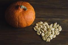 Pumpkin seeds. Heart shaped dried pumpkin seeds and a little pumpkin on a brown table Royalty Free Stock Photos