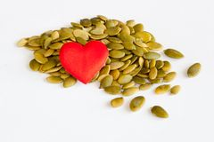 Pumpkin seeds. And a heart on white background Royalty Free Stock Photography