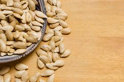 Pumpkin seeds inside a small bowl, with some seeds below, on a light wooden surface. Pumpkin seeds inside a small bowl, with some seeds below, on a light wooden stock photo