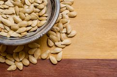 Pumpkin seeds inside a small bowl, with some seeds below, on a two-colored wooden surface. Pumpkin seeds inside a small bowl, with some seeds below, on a two royalty free stock image