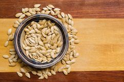 Pumpkin seeds inside a small bowl, some spread seeds below, on a two-colored wooden surface. top view. Pumpkin seeds inside a small bowl, some spread seeds royalty free stock photo