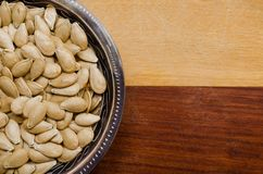 Pumpkin seeds inside a small bowl on a two-colored wooden surface. Pumpkin seeds inside a small bowl on a two-colored wooden surface royalty free stock photography