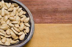 Pumpkin seeds inside a small bowl on a two-colored wooden surface. Pumpkin seeds inside a small bowl on a two-colored wooden surface stock photos