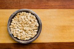 Pumpkin seeds inside a small bowl on a two-colored wooden surface. top view. Pumpkin seeds inside a small bowl on a two-colored wooden surface. top view royalty free stock images