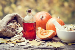 Pumpkin seeds oil bottle, pumpkins, bag with seeds and mortar. Pumpkin seeds oil bottle, pumpkins, canvas bag with seeds and mortar on wooden table. Selective Royalty Free Stock Photography