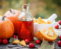 Pumpkin seeds oil bottle, pumpkins, hawthorn berries and mortar. On wooden table with autumn leaves. Selective focus Stock Photos