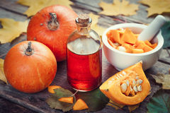 Pumpkin seeds oil bottle, pumpkins and mortar on wooden table Royalty Free Stock Photo