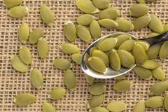 Pumpkin seeds or pips on a dessert spoon royalty free stock images