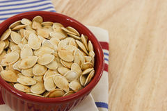 Pumpkin seeds in a red bowl with copy-space Royalty Free Stock Photos