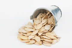 Pumpkin seeds spilling out of bucket Royalty Free Stock Photos