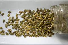 Pumpkin seeds spilling out of container, from above, close Royalty Free Stock Image
