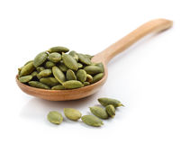 Pumpkin seeds in the spoon on white background Stock Photo