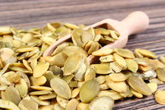 Pumpkin seeds with spoon on wooden background Stock Image