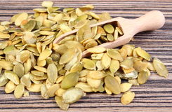 Pumpkin seeds with spoon on wooden background Royalty Free Stock Photo