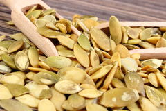 Pumpkin seeds with spoon on wooden background Royalty Free Stock Image