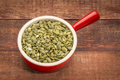 Pumpkin seeds in a stoneware cup Royalty Free Stock Photography