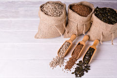 Pumpkin seeds, sunflower and flax seeds in wooden spoon. In the background jute bag with seeds. Stock Photo