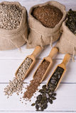 Pumpkin seeds, sunflower and flax seeds in wooden spoon. In the background jute bag with seeds. Stock Images