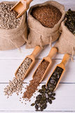 Pumpkin seeds, sunflower and flax seeds in wooden spoon. In the background jute bag with seeds. Stock Photography