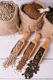 Pumpkin seeds, sunflower and flax seeds in wooden spoon. In the background jute bag with seeds. Stock Photos