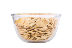 Pumpkin seeds in a transparent bowl isolated on white background Stock Images