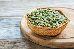 Pumpkin seeds in a wicker basket Stock Images