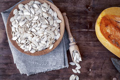 Pumpkin seeds in a wooden bowl with a piece of fresh pumpkin Stock Images