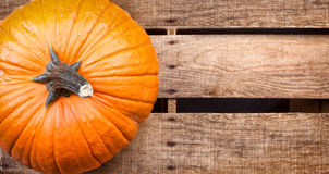 Pumpkin sitting on wooden crate Royalty Free Stock Photography