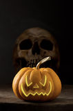 Pumpkin and skull. Halloween pumpkin , the real pumpkin and skull at behind on old wood with illustration of evil face on dark background royalty free stock photo