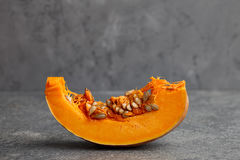 Pumpkin slice with seeds on textured stone background. Halloween pumpkin slice with seeds on gray textured stone background Royalty Free Stock Photography