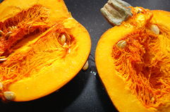 Pumpkin sliced on black background. royalty free stock photography