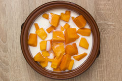 Pumpkin sliced in clay pot with milk Royalty Free Stock Photos