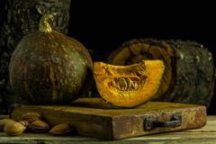 A pumpkin sliced on an old chopping board. And some nuts Stock Photos