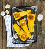 Pumpkin slices for baking with oregano, onion, garlic and olive royalty free stock photography