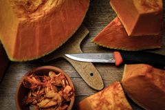 Pumpkin slices and seeds in the ceramic bowl on wooden table royalty free stock photography