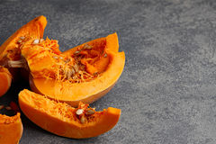 Pumpkin slices with seeds on textured stone background. Halloween pumpkin slices with seeds on gray textured stone background Stock Photos