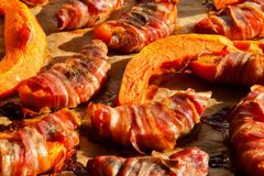 Pumpkin slices wrapped in bacon and baked Stock Photo