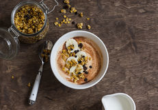 Pumpkin smoothie bowl with banana and granola on wooden table, top view. Royalty Free Stock Photo