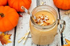 Pumpkin smoothie in a mason jar, scene on white wood. Pumpkin smoothie in a mason jar with coconut and cinnamon, scene on rustic white wood Royalty Free Stock Photography