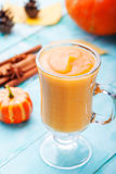 Pumpkin smoothie with pie spices on a turquoise wooden background Royalty Free Stock Photo