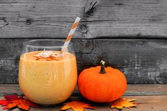 Pumpkin smoothie, scene on rustic wood. Pumpkin smoothie with coconut and cinnamon, scene on a rustic wooden background Royalty Free Stock Image
