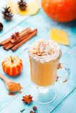 Pumpkin smoothie, spice latte with whipped cream. Turquoise wooden background. Stock Photo